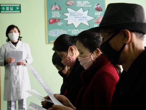 북한 평양의 평천구역병원에서 코로나 바이스러에 대한 설명을 듣고 있는 주민들.