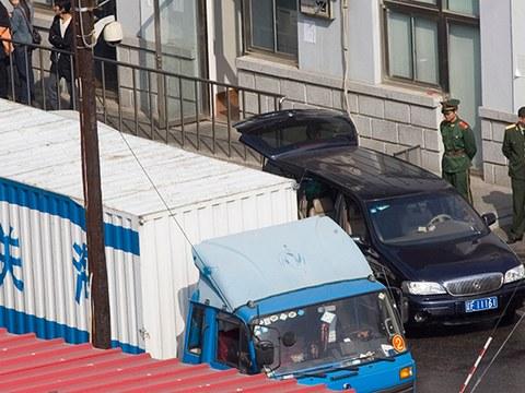 중국 공안이 단둥세관을 통과해서 북한으로 가는 차량들을 지켜보고 있다.