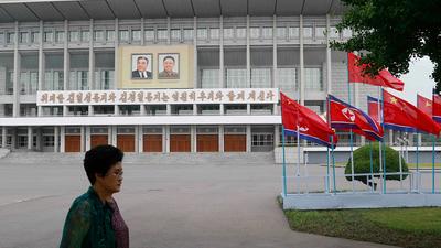 북한 주민이 구호가 적힌 건물 앞으로 지나가고 있다.