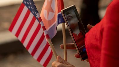 베트남 하노이에서 한 여성이 미국과 북한 국기를 들고 걷고 있다.