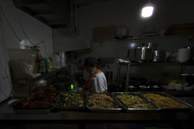 정전사태로 중국 선양의 한 식당에서 여성이 이동식 배터리를 이용해 전구를 켜고 요리를 하고 있다.