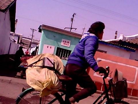 함경북도 청진시에서 한 여성이 자전거를 타고 수남시장으로 가고 있다.